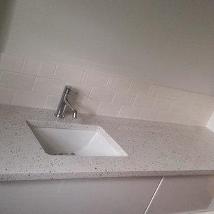 Imagen de cuarto de baño con ducha, escandinavo, de tamaño medio, con armarios con paneles lisos, puertas de armario blancas, ducha empotrada, sanitario de una pieza, baldosas y/o azulejos blancos, baldosas y/o azulejos de cemento, paredes blancas, lavabo bajoencimera y encimera de terrazo