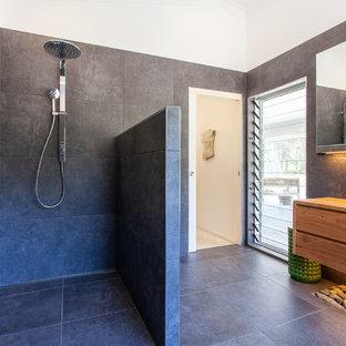 Imagen de cuarto de baño principal, contemporáneo, grande, con armarios tipo vitrina, puertas de armario de madera oscura, bañera exenta, ducha abierta, baldosas y/o azulejos grises, baldosas y/o azulejos de cerámica, paredes grises, suelo de baldosas de cerámica, encimera de madera, suelo gris y ducha abierta