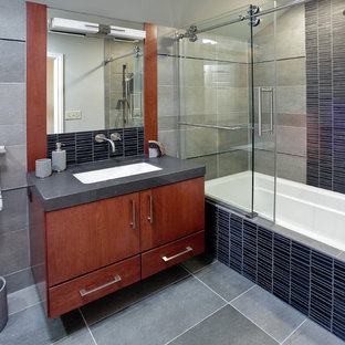 Inspiration for a contemporary black tile and matchstick tile bathroom remodel in Milwaukee with an undermount sink, flat-panel cabinets and medium tone wood cabinets