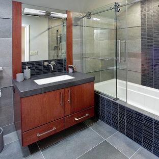Стильный дизайн: ванная комната в современном стиле с врезной раковиной, плоскими фасадами, фасадами цвета дерева среднего тона, ванной в нише, душем над ванной, черной плиткой и удлиненной плиткой - последний тренд