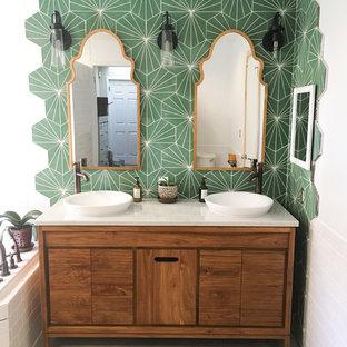 Modelo de cuarto de baño principal, bohemio, de tamaño medio, con armarios tipo mueble, puertas de armario de madera oscura, baldosas y/o azulejos verdes, paredes blancas, suelo de baldosas de porcelana, lavabo sobreencimera, encimera de cuarcita, suelo gris y encimeras blancas