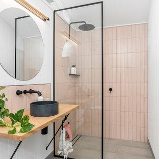 Imagen de cuarto de baño con ducha, contemporáneo, de tamaño medio, con ducha a ras de suelo, baldosas y/o azulejos rosa, lavabo sobreencimera, encimera de madera, suelo gris, ducha abierta y encimeras beige