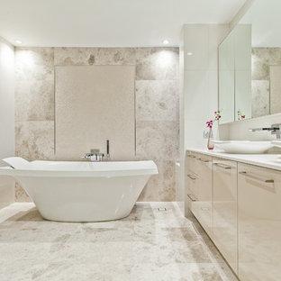 Inspiration för moderna badrum, med ett fristående handfat, släta luckor, beige skåp, ett fristående badkar, beige kakel och beige väggar