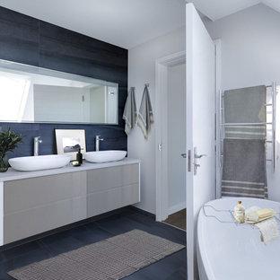 Ispirazione per una stanza da bagno padronale minimal di medie dimensioni con ante lisce, ante beige, vasca freestanding, doccia ad angolo, piastrelle grigie, piastrelle in travertino, top in laminato, porta doccia scorrevole e top bianco