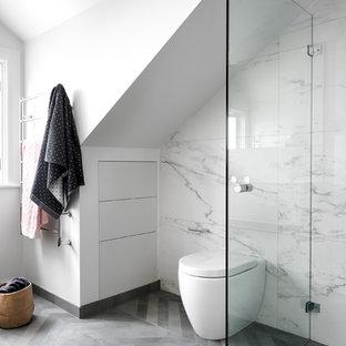 Inredning av ett modernt mellanstort en-suite badrum, med vita skåp, en toalettstol med hel cisternkåpa, grå kakel, porslinskakel, vita väggar, klinkergolv i porslin, släta luckor och med dusch som är öppen