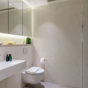 Photo of a small contemporary ensuite bathroom in London with a wall mounted toilet, grey tiles, grey walls, a wall-mounted sink, grey floors and an open shower.