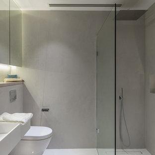 Diseño de cuarto de baño principal, minimalista, pequeño, con armarios con paneles empotrados, puertas de armario grises, ducha abierta, sanitario de pared, baldosas y/o azulejos grises, baldosas y/o azulejos de porcelana, paredes grises, suelo de azulejos de cemento, lavabo suspendido, encimera de cemento, suelo gris, ducha abierta y encimeras grises