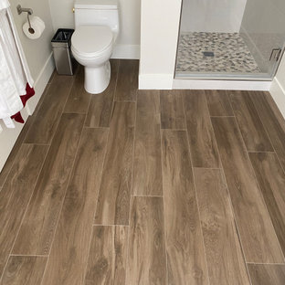 Photo of a mid-sized contemporary master bathroom in San Francisco with shaker cabinets, dark wood cabinets, a freestanding tub, an alcove shower, a one-piece toilet, beige tile, porcelain tile, beige walls, wood-look tile, an undermount sink, engineered quartz benchtops, brown floor, a hinged shower door, multi-coloured benchtops, a double vanity and a built-in vanity.