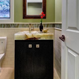 Modelo de cuarto de baño de estilo americano, pequeño, con armarios tipo mueble, puertas de armario negras, sanitario de dos piezas, baldosas y/o azulejos verdes, baldosas y/o azulejos de vidrio laminado, paredes verdes, suelo de baldosas de cerámica, lavabo integrado, encimera de ónix y suelo beige