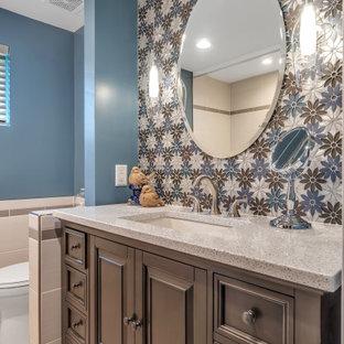 セントルイスの小さいコンテンポラリースタイルのおしゃれな子供用バスルーム (フラットパネル扉のキャビネット、茶色いキャビネット、アルコーブ型浴槽、シャワー付き浴槽、一体型トイレ、マルチカラーのタイル、モザイクタイル、青い壁、セラミックタイルの床、アンダーカウンター洗面器、珪岩の洗面台、グレーの床、シャワーカーテン、白い洗面カウンター) の写真