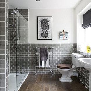 Bild på ett mellanstort vintage badrum, med en dusch i en alkov, en toalettstol med separat cisternkåpa, grå kakel, tunnelbanekakel, vita väggar, mellanmörkt trägolv, ett piedestal handfat, brunt golv och dusch med gångjärnsdörr