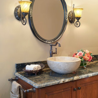 Mid-sized mediterranean master bathroom in New York with a vessel sink, raised-panel cabinets, medium wood cabinets, granite benchtops, beige walls, beige tile, an alcove shower, a two-piece toilet, stone slab and travertine floors.