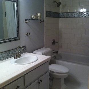 シアトルの小さいトランジショナルスタイルのおしゃれな子供用バスルーム (オーバーカウンターシンク、シェーカースタイル扉のキャビネット、青いキャビネット、タイルの洗面台、ドロップイン型浴槽、シャワー付き浴槽、分離型トイレ、マルチカラーのタイル、ガラスタイル、青い壁、セラミックタイルの床) の写真