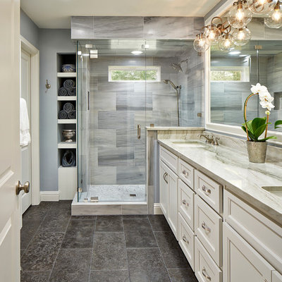 Elegant master gray tile corner shower photo in Dallas with white cabinets, an undermount sink, recessed-panel cabinets and gray walls