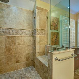 Diseño de cuarto de baño principal, tradicional, grande, con lavabo bajoencimera, armarios con paneles con relieve, puertas de armario de madera en tonos medios, encimera de cuarzo compacto, ducha esquinera, sanitario de una pieza, baldosas y/o azulejos beige, paredes amarillas y suelo de baldosas de cerámica