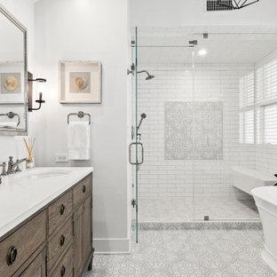 Idéer för stora vintage vitt en-suite badrum, med möbel-liknande, ett fristående badkar, vit kakel, tunnelbanekakel, vita väggar, klinkergolv i porslin, flerfärgat golv, skåp i mörkt trä, en dusch i en alkov, ett undermonterad handfat och dusch med gångjärnsdörr