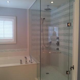 Foto de cuarto de baño con ducha, minimalista, de tamaño medio, con armarios con paneles lisos, puertas de armario blancas, bañera encastrada, ducha esquinera, sanitario de una pieza, baldosas y/o azulejos grises, azulejos en listel, paredes púrpuras, suelo de baldosas de cerámica, lavabo bajoencimera y encimera de acrílico