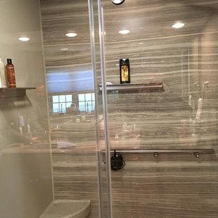 Foto de cuarto de baño principal, clásico renovado, con armarios con paneles con relieve, puertas de armario de madera oscura, sanitario de dos piezas, suelo laminado, lavabo integrado, encimera de ónix y suelo gris