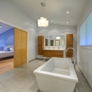 Modelo de cuarto de baño principal, asiático, de tamaño medio, con lavabo suspendido, bañera exenta, ducha abierta, sanitario de pared, baldosas y/o azulejos grises y paredes grises
