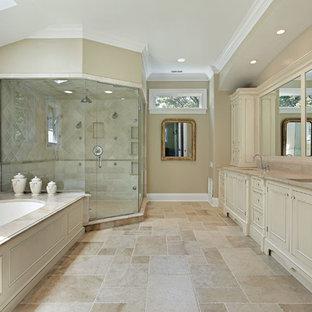 Modelo de cuarto de baño principal, grande, con armarios estilo shaker, puertas de armario blancas, bañera encastrada sin remate, ducha esquinera, bidé, baldosas y/o azulejos beige, baldosas y/o azulejos de piedra, paredes marrones, suelo de travertino, lavabo bajoencimera y encimera de mármol