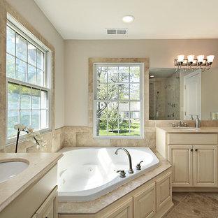 Ispirazione per una stanza da bagno padronale classica di medie dimensioni con ante in stile shaker, ante beige, vasca idromassaggio, piastrelle beige, piastrelle in pietra, pareti marroni, pavimento in travertino, lavabo sottopiano e top in pietra calcarea