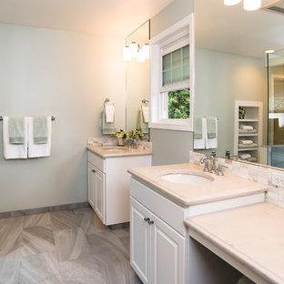 Ejemplo de cuarto de baño principal, clásico, grande, con lavabo bajoencimera, armarios con paneles con relieve, puertas de armario blancas, encimera de cuarcita, ducha esquinera, baldosas y/o azulejos beige, suelo de baldosas tipo guijarro, paredes blancas y suelo de baldosas de cerámica
