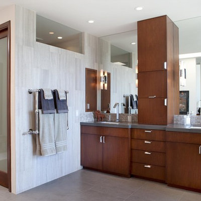 Inspiration for a large contemporary master gray tile and porcelain tile porcelain tile and gray floor freestanding bathtub remodel in Los Angeles with an undermount sink, flat-panel cabinets, dark wood cabinets, solid surface countertops, white walls, a one-piece toilet and gray countertops