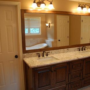 カンザスシティのモダンスタイルのおしゃれな浴室 (レイズドパネル扉のキャビネット、濃色木目調キャビネット、オレンジの壁、大理石の洗面台、オレンジの床、白い洗面カウンター) の写真