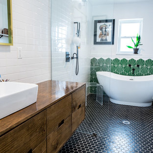 Bathroom - eclectic master green tile black floor bathroom idea in Houston with flat-panel cabinets, medium tone wood cabinets, white walls, a vessel sink, wood countertops and brown countertops