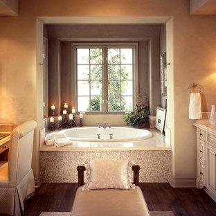 Diseño de cuarto de baño principal, clásico, grande, con armarios con rebordes decorativos, puertas de armario beige, bañera encastrada, paredes beige, suelo de madera oscura, lavabo bajoencimera, encimera de cuarzo compacto, suelo marrón y encimeras beige