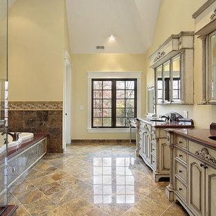 Свежая идея для дизайна: огромная главная ванная комната в классическом стиле с фасадами островного типа, искусственно-состаренными фасадами, накладной ванной, открытым душем, бежевой плиткой, коричневой плиткой, каменной плиткой, желтыми стенами, врезной раковиной, столешницей из гранита, разноцветным полом, душем с распашными дверями и красной столешницей - отличное фото интерьера
