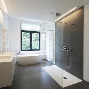 ロサンゼルスの中くらいのモダンスタイルのおしゃれなマスターバスルーム (フラットパネル扉のキャビネット、白いキャビネット、置き型浴槽、バリアフリー、スレートタイル、白い壁、スレートの床、一体型シンク、人工大理石カウンター、黒い床、オープンシャワー) の写真