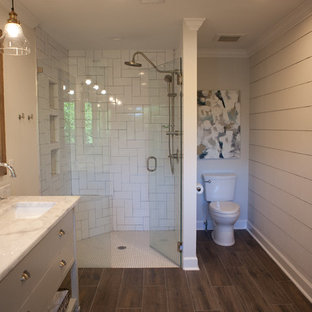Großes Modernes Badezimmer En Suite mit verzierten Schränken, weißen Schränken, Eckdusche, Toilette mit Aufsatzspülkasten, weißen Fliesen, Metrofliesen, dunklem Holzboden, Marmor-Waschbecken/Waschtisch, grauer Wandfarbe, braunem Boden, Falttür-Duschabtrennung und Unterbauwaschbecken in Atlanta