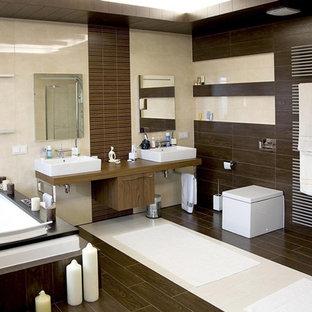 Идея дизайна: большая главная ванная комната в современном стиле с фасадами в стиле шейкер, фасадами цвета дерева среднего тона, накладной ванной, биде, коричневой плиткой, керамогранитной плиткой, бежевыми стенами, полом из керамогранита, настольной раковиной, столешницей из дерева, коричневым полом, бежевой столешницей, тумбой под две раковины, подвесной тумбой и многоуровневым потолком