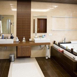 Неиссякаемый источник вдохновения для домашнего уюта: большая главная ванная комната в современном стиле с фасадами в стиле шейкер, фасадами цвета дерева среднего тона, накладной ванной, биде, коричневой плиткой, керамогранитной плиткой, бежевыми стенами, полом из керамогранита, настольной раковиной, столешницей из дерева, коричневым полом, бежевой столешницей, тумбой под две раковины, подвесной тумбой и многоуровневым потолком
