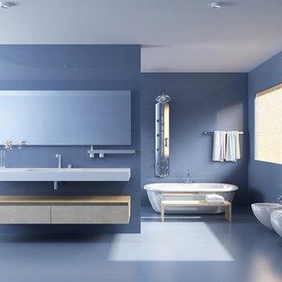 Diseño de cuarto de baño principal, minimalista, grande, con armarios con paneles lisos, puertas de armario beige, bañera exenta, sanitario de una pieza, baldosas y/o azulejos azules, baldosas y/o azulejos de porcelana, paredes azules, suelo de baldosas de cerámica, lavabo integrado y encimera de cuarcita