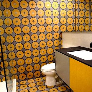 ロサンゼルスの中サイズのトランジショナルスタイルのおしゃれなバスルーム (浴槽なし) (フラットパネル扉のキャビネット、オレンジのキャビネット、コーナー設置型シャワー、分離型トイレ、オレンジのタイル、セラミックタイル、オレンジの壁、セラミックタイルの床、オーバーカウンターシンク、クオーツストーンの洗面台、オレンジの床、開き戸のシャワー、黒い洗面カウンター) の写真