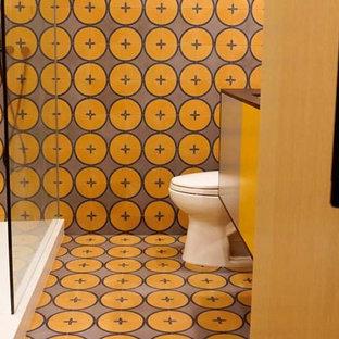 ロサンゼルスの中くらいのトランジショナルスタイルのおしゃれなバスルーム (浴槽なし) (フラットパネル扉のキャビネット、オレンジのキャビネット、アルコーブ型シャワー、分離型トイレ、オレンジのタイル、セラミックタイル、オレンジの壁、セラミックタイルの床、オーバーカウンターシンク、オレンジの床、開き戸のシャワー、オレンジの洗面カウンター) の写真