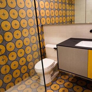 ロサンゼルスの中くらいのトランジショナルスタイルのおしゃれなバスルーム (浴槽なし) (フラットパネル扉のキャビネット、オレンジのキャビネット、コーナー設置型シャワー、分離型トイレ、オレンジのタイル、セラミックタイル、オレンジの壁、セラミックタイルの床、オーバーカウンターシンク、クオーツストーンの洗面台、オレンジの床、開き戸のシャワー、黒い洗面カウンター) の写真