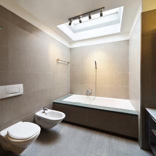 Ispirazione per una stanza da bagno padronale minimal di medie dimensioni con ante lisce, ante nere, vasca da incasso, bidè, piastrelle grigie, pareti beige, pavimento in legno verniciato, lavabo a bacinella, top in vetro e doccia aperta