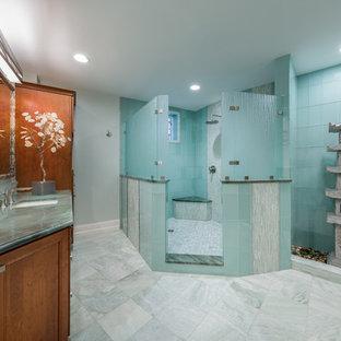 Modelo de cuarto de baño principal, de estilo zen, grande, con armarios con rebordes decorativos, puertas de armario de madera oscura, ducha abierta, baldosas y/o azulejos azules, baldosas y/o azulejos de vidrio, paredes azules, suelo de baldosas de porcelana, lavabo bajoencimera y encimera de azulejos