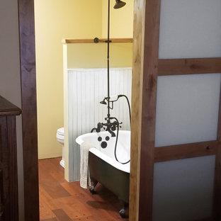 Idée de décoration pour une salle de bain principale chalet de taille moyenne avec meuble-lavabo sur pied, un placard en trompe-l'oeil, des portes de placard en bois brun, une baignoire sur pieds, un combiné douche/baignoire, un WC séparé, un mur jaune, un sol en bois brun, un lavabo posé, un plan de toilette en bois, un sol marron, une cabine de douche avec un rideau, un plan de toilette marron, meuble double vasque et du lambris.