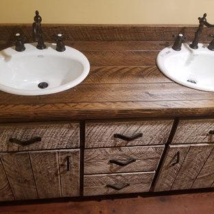 Inspiration för mellanstora rustika brunt en-suite badrum, med möbel-liknande, skåp i mellenmörkt trä, ett badkar med tassar, en dusch/badkar-kombination, en toalettstol med separat cisternkåpa, gula väggar, mellanmörkt trägolv, ett nedsänkt handfat, träbänkskiva, brunt golv och dusch med duschdraperi