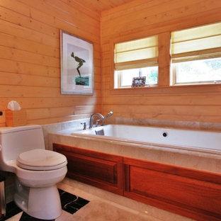 Klassisk inredning av ett badrum, med ett nedsänkt handfat, luckor med upphöjd panel, skåp i mellenmörkt trä, ett platsbyggt badkar och beige kakel