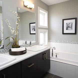 オレンジカウンティの中くらいのトラディショナルスタイルのおしゃれなマスターバスルーム (フラットパネル扉のキャビネット、濃色木目調キャビネット、ドロップイン型浴槽、分離型トイレ、グレーのタイル、白いタイル、磁器タイル、グレーの壁、磁器タイルの床、アンダーカウンター洗面器、ラミネートカウンター、グレーの床) の写真