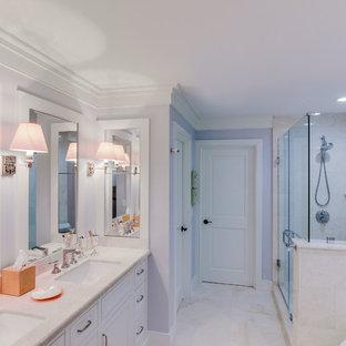 Foto di una stanza da bagno con vasca freestanding, doccia ad angolo, piastrelle bianche, pareti viola, pavimento in pietra calcarea e lavabo da incasso