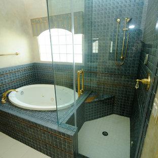 На фото: большая главная ванная комната в викторианском стиле с фасадами с утопленной филенкой, желтыми фасадами, накладной ванной, душем в нише, раздельным унитазом, коричневой плиткой, керамогранитной плиткой, желтыми стенами, полом из керамогранита, настольной раковиной, мраморной столешницей, белым полом и душем с распашными дверями с