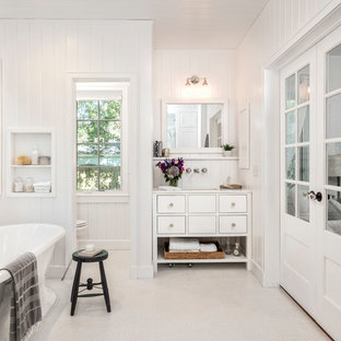 Inspiration for a medium sized rural ensuite bathroom with flat-panel cabinets, white cabinets, a freestanding bath, a two-piece toilet, white tiles, white walls, mosaic tile flooring, a submerged sink, engineered stone worktops and white floors.