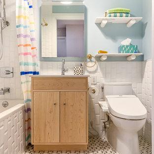 Cette image montre une salle de bain traditionnelle avec un placard à porte plane, des portes de placard en bois clair, une baignoire en alcôve, un combiné douche/baignoire, un carrelage blanc, un carrelage métro, un mur bleu, un sol multicolore, une cabine de douche avec un rideau, un plan de toilette jaune, meuble simple vasque et meuble-lavabo encastré.