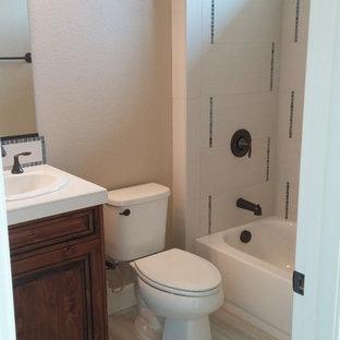 Foto di una stanza da bagno con doccia classica di medie dimensioni con ante in legno bruno, vasca ad alcova, vasca/doccia, WC a due pezzi, piastrelle bianche, piastrelle in gres porcellanato, pareti beige, pavimento in gres porcellanato, lavabo da incasso e top piastrellato